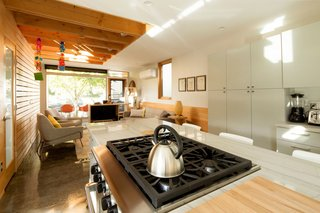 8 Modern In-Law Units - Photo 12 of 16 - The interior of the 800-square-foot ADU melds the warmth of exposed-wood framing with crisp white finishes in an efficient kitchen.