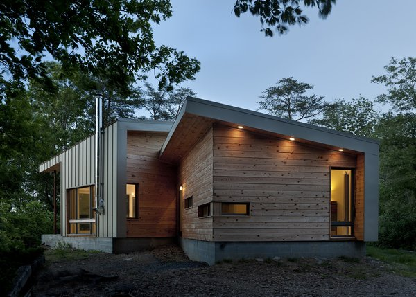 Designed by GriD architects, this weekend retreat perched on a ridge overlooking the Potomac River optimizes both east-west exposure and views of the river. Its exterior cladding of wood and green-painted metal siding allude to the home's connection to its surroundings.