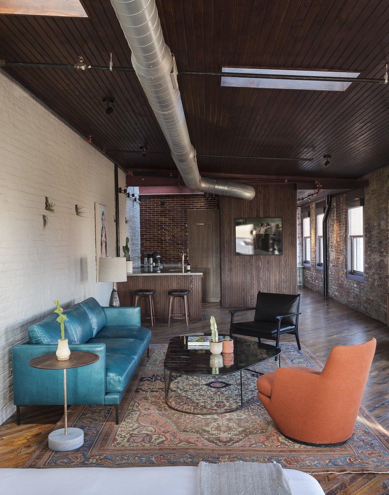 Living Room, Chair, End Tables, Sofa, Lamps, Bar, Stools, and Medium Hardwood Floor  Mulherin's Hotel