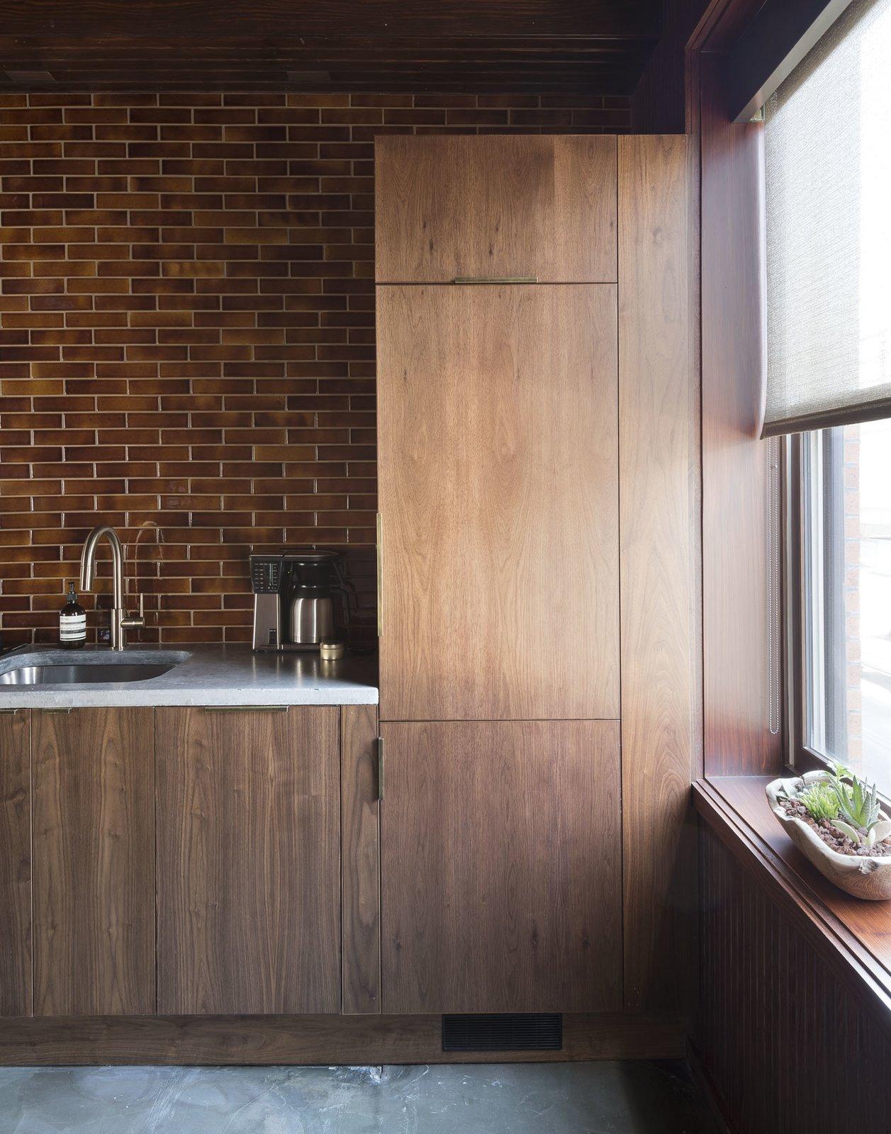 Kitchen, Wood Cabinet, Concrete Floor, Granite Counter, Ceramic Tile Backsplashe, Accent Lighting, Drop In Sink, and Refrigerator  Mulherin's Hotel