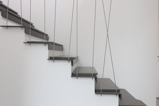 9 Unique Stair Railings - Photo 1 of 9 - In Geneva, an existing wooden stair is transformed with a steel tread topped with a plank of concrete. The distinctly modern feel extends to the steel tension rods that cross each other to create an irregular pattern.