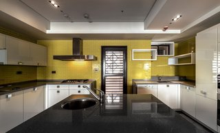 The yellow wall tiles in the kitchen were custom hand-made with glass and applied with enamel. They present a different sparkling and mirror effect which meets the expectations of the female owner for a modern atmosphere.