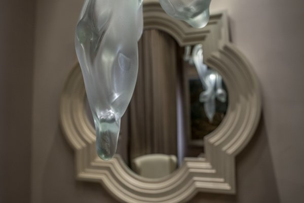 Contemporary glass fixtures with fluid, natural shapes harmoniously blend with the more traditional elements found in throughout the house.