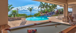 Rainbow Estate is a luxurious vacation rental located in Maui, hosting gorgeous Pacific Ocean views. This four bedroom estate has an ability to sleep up to 10 guests in comfort, surrounded by a host of fun vacation amenities. The king master suite is divine with a deluxe en suite bathroom and complete privacy. The two private queen suites are lovely and share a luxurious bathroom. The fourth bedroom is loft-style with two double beds; perfect for children, and adjacent to the indoor movie theater.