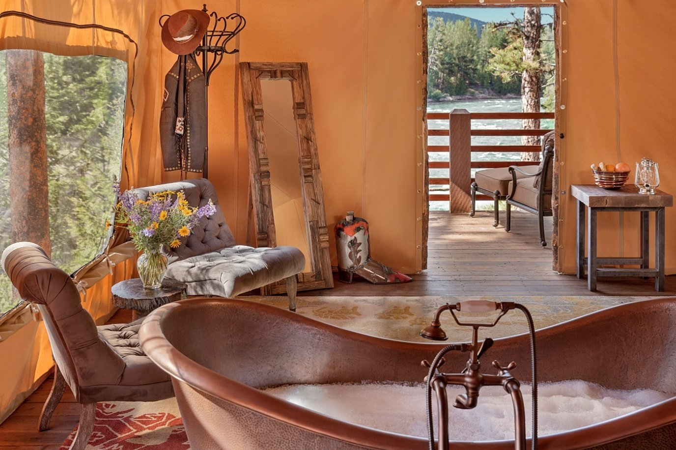 Outdoor, Woodland, Trees, Horizontal Fences, Wall, Decking Patio, Porch, Deck, and Wood Patio, Porch, Deck At this sprawling resort just east of Missoula, honeymooning couples can choose between six glamping tents, each fitted with a king bed, jetted tubs/showers, and luxury resort amenities. Honeymooners will definitely want to book the Tango Point tent. In addition to its prime location along the banks of the scenic Blackfoot River, the suite comes with heated slate floors, a dining pavilion with fireplace and lounge, plus your very own camping butler.  Photo 6 of 14 in 12 Terrifically Glamorous Camping Options