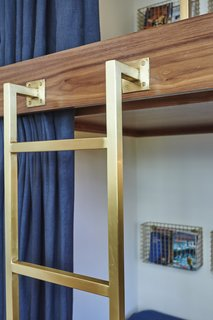 Sarah Barnard designed the custom brushed brass ladder and bed rail to complement the antique metal finishes.