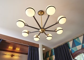 The vintage inspired brass and black chandelier makes the room glow with warm diffuse light.