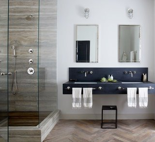 Subtler shading works here for New York City–based designer Jenny Wolf, who used mirrors and patterns for this windowless bathroom. Tall mirrored medicine cabinets and a glass shower amplify light from the interior fixtures, brightening up the space. Wolf used built-in cabinets to save floor space. A herringbone wood floor gives the illusion of a larger and warmer bath.