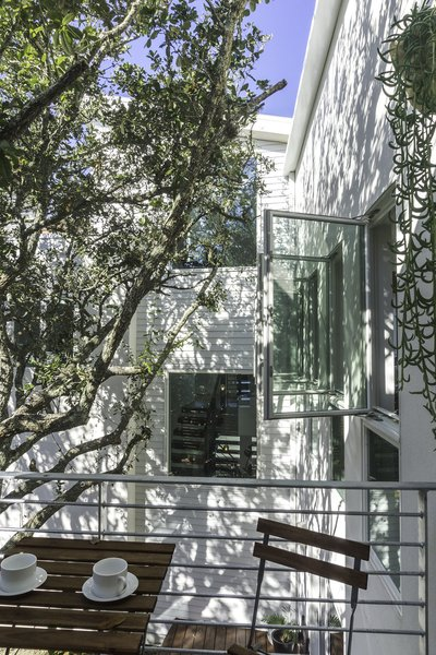 Master balcony designed to give the experience of being in and living below the canopy of a tree.  The windows are positioned and oriented to allow the ocean breezes to flow through the home