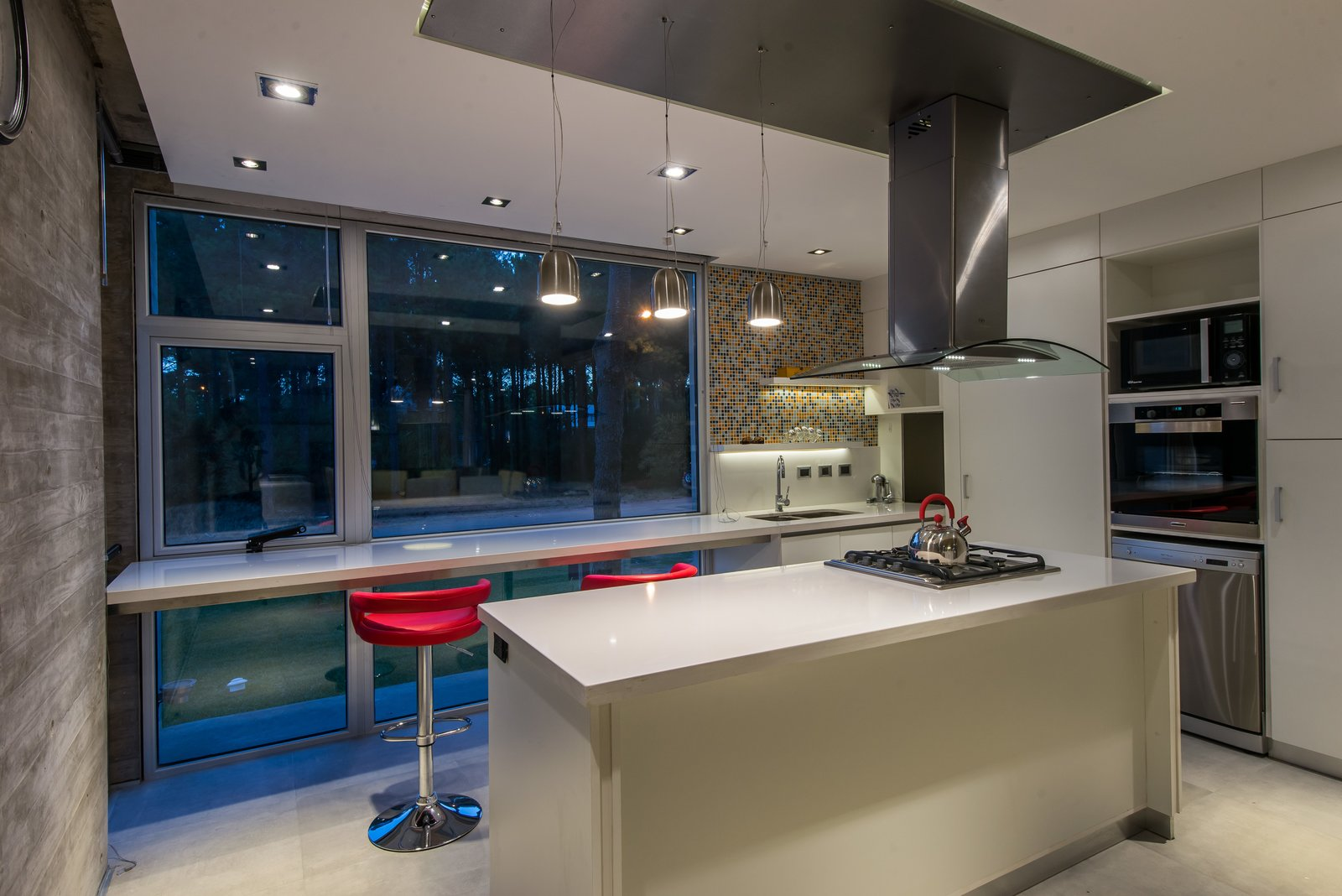 Kitchen, Quartzite Counter, White Cabinet, Porcelain Tile Floor, Mosaic Tile Backsplashe, Wall Oven, Ceiling Lighting, Refrigerator, Cooktops, Drop In Sink, Microwave, and Dishwasher  Casa Batin by Estudio Galera