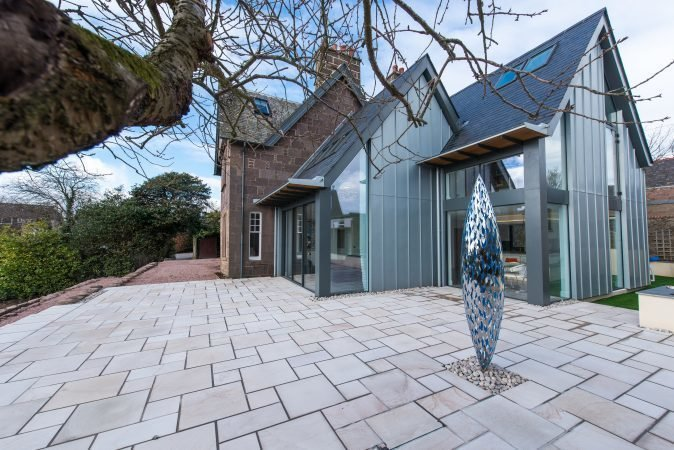 In 2016 Hyve Architects completed the renovation of The Gables, a heritage home in Stonehaven. A modern extension features an open kitchen and family room that connects to the main stone home. The double pitched roofline of the new structure references the end gable line of the original house. Tagged: Exterior, Metal Siding Material, House, Glass Siding Material, Stone Siding Material, and Shingles Roof Material.  Photo 6 of 11 in Merging Old and New With These 10 Modern Renovations in Scotland