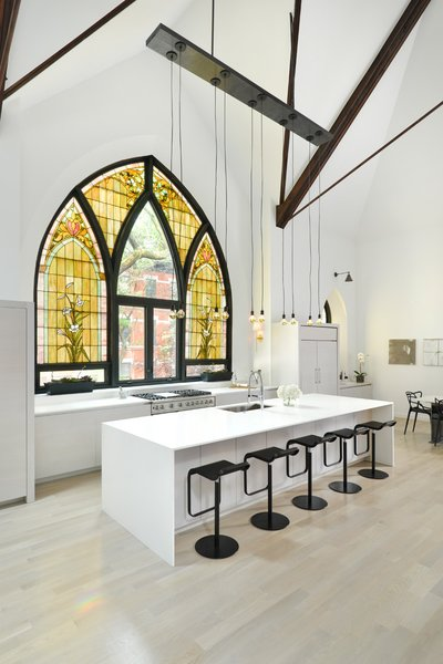 This church conversion in Chicago was completed by Linc Thelen Design and Scrafano Architects, and transformed the brick church into a single-family home. Arched stained glass windows were maintained, and some panels were swapped out for clear glass. Tagged: Kitchen, Undermount Sink, Range, Refrigerator, White Cabinet, Light Hardwood Floor, Pendant Lighting, and Wall Lighting.  Photo 5 of 9 in 7 Repurposed Churches Around the World