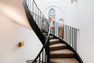 In the London neighborhood of Kenmont Gardens, a brick church's stained-glass windows provide a pop of color. It contrasts with the surrounding stark white walls and black powder-coated steel spiral staircase that connects the open-plan main level of the home to the bedrooms on the upper floors.