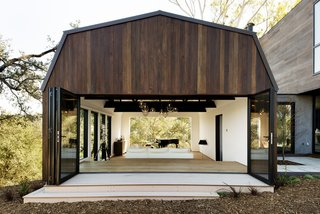 To make the common gambrel roof more contemporary, architecture firm Walker Workshop played with the typical proportions of a gambrel roof to make it wider.