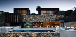 The rear of the house has a pool and patio that features smooth concrete, which contrasts with the varied texture and color of the stone walls.