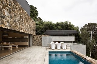 Stone walls surround the patio area and the edge of the pool.