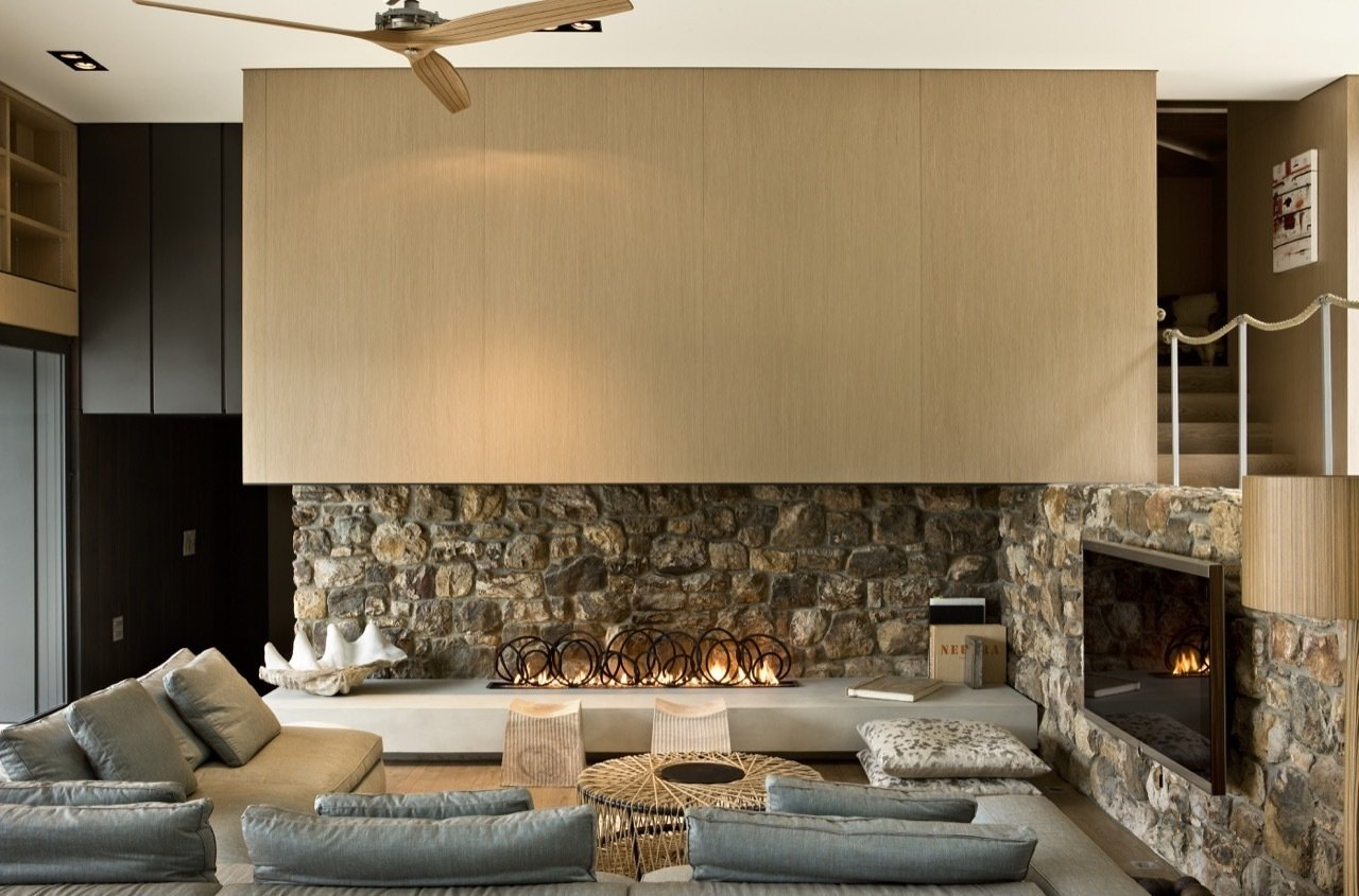 Local stone was used on selective interior walls as well as the exterior. Tagged: Living Room, Gas Burning Fireplace, Sectional, Recessed Lighting, Coffee Tables, and Light Hardwood Floor.  Photo 4 of 16 in These 4 Modern Homes Around the World Take Advantage of Local Stone