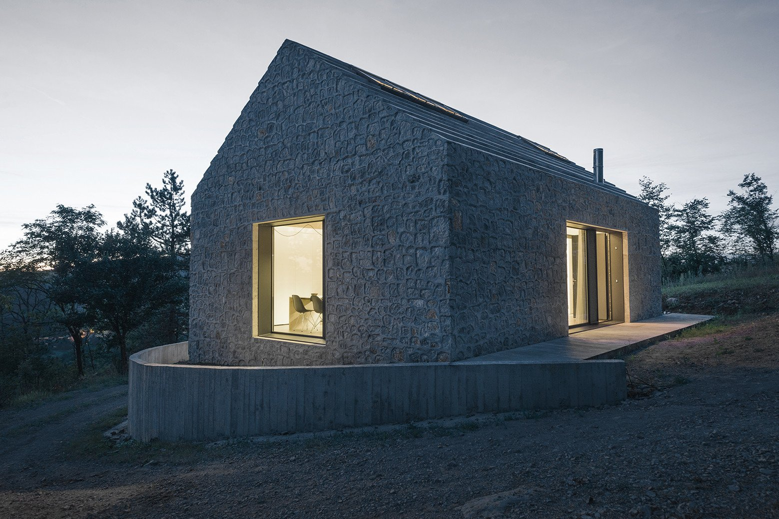 A stepped concrete roof continues the varied texture of the house's exterior. Tagged: Exterior, Cabin Building Type, and Stone Siding Material.  Photo 8 of 16 in These 4 Modern Homes Around the World Take Advantage of Local Stone