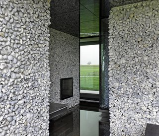 On the upper floor, smaller stones of lighter colored flint cover the walls.