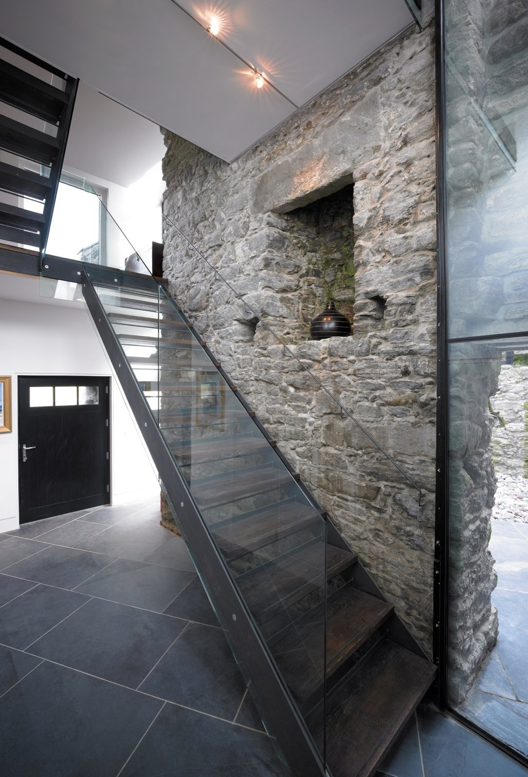 Staircase, Wood Tread, and Glass Railing On the interior, existing stone walls are often left exposed  Photo 5 of 19 in Rising From the Ruins: Homes Built on Architectural Remains