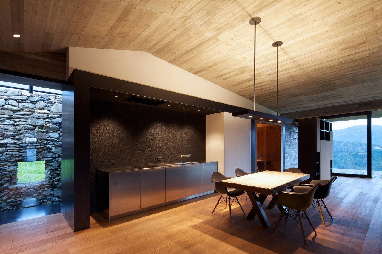Kitchen, Stone Tile Backsplashe, Medium Hardwood Floor, and Track Lighting On the interior, views of both the old stone wall and the landscape beyond are emphasized.  Photo 9 of 19 in Rising From the Ruins: Homes Built on Architectural Remains