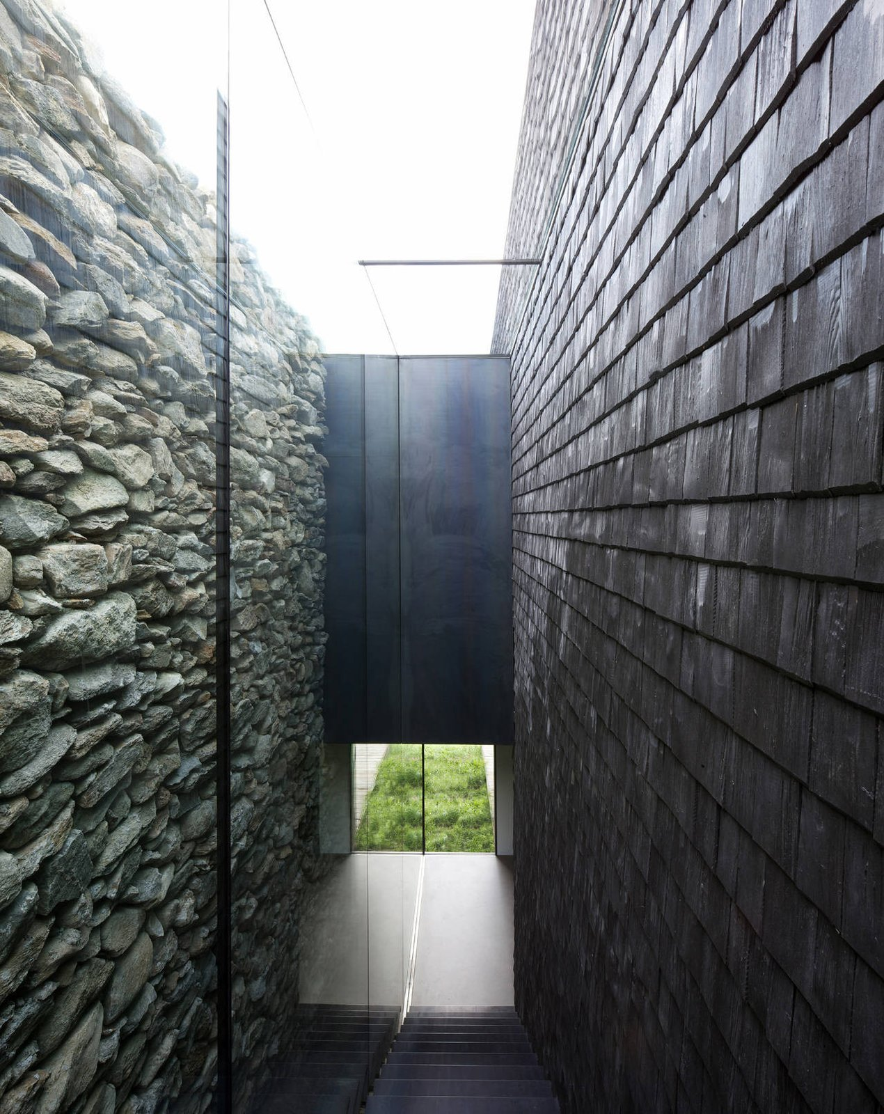 Staircase and Wood Tread An open-air corridor is formed between the old stone walls and the new wooden shingles.  Photo 8 of 19 in Rising From the Ruins: Homes Built on Architectural Remains