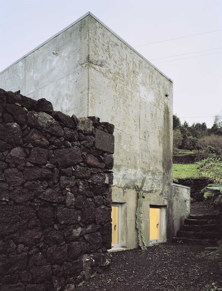 The concrete structure was designed to fit within the existing dark volcanic rock walls.  Photo 16 of 19 in Rising From the Ruins: Homes Built on Architectural Remains