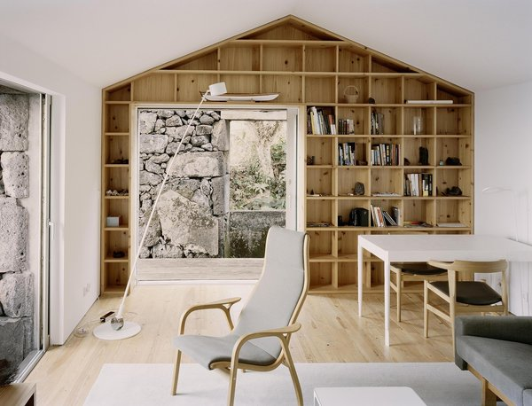The interiors frame selective views of the existing rock walls, and contrast them with light finishes of white walls and wood furniture and shelving.  Photo 19 of 19 in Rising From the Ruins: Homes Built on Architectural Remains