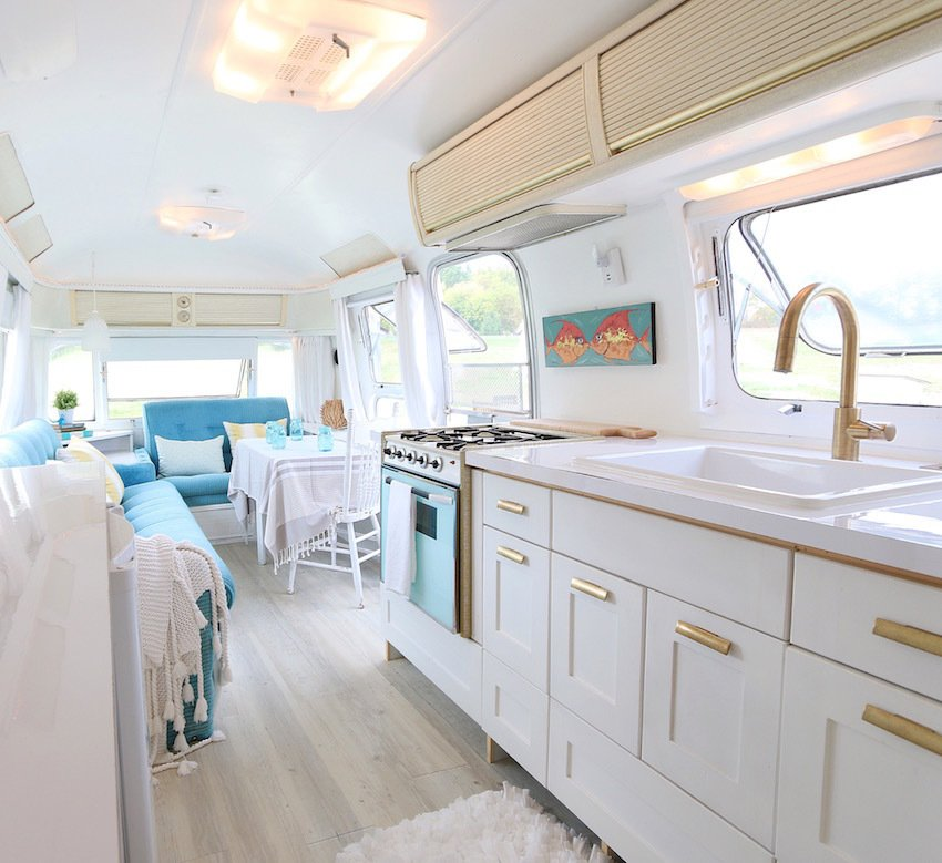 Kitchen, White Cabinet, Drop In Sink, Range, Ceiling Lighting, Wall Oven, Accent Lighting, Rug Floor, and Light Hardwood Floor Designer and writer Lynne Knowlton revamped her 1976 Airstream with a girly edge -- without once using any lace or pink. By consistently using brushed gold hardware, tufted blue seating (which even appears to be original!), and casually-thrown fringed blankets, the space is packed with effortless personality. Light-colored wide plank flooring and white paint keep the space light and airy.  Photo 4 of 8 in These 7 Vintage Airstreams Were Transformed Into Modern Escapes