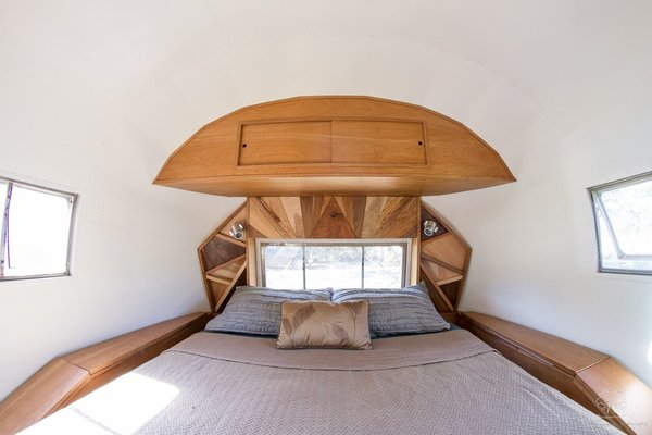 A custom headboard made of triangular pieces of black walnut is the clear hero of this 1954 Airstream renovation by ArtisTree, a designer of custom treetop and small-space homes. Because sustainability was a priority in this project, the floors are made of recycled wood (treated with the Japanese burning technique, sho-sugi-ban, to darken them), and the tiles in the bathroom are created from recycled glass.
