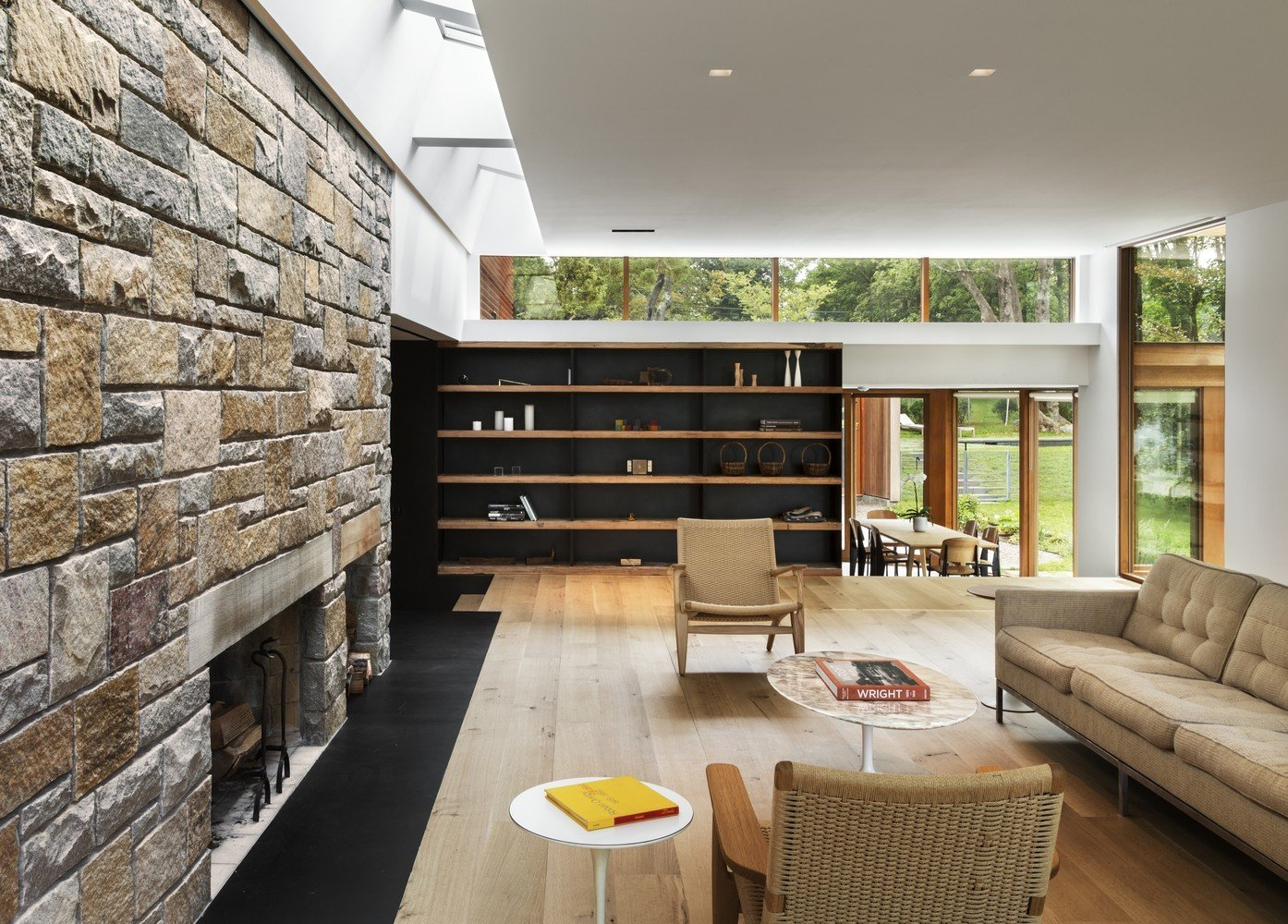Living Room, Wood Burning Fireplace, Chair, Shelves, Sofa, Light Hardwood Floor, and Standard Layout Fireplace In this house by architecture firm Joeb Moore & Partners, the ceiling acts as a large light shelf, distributing an even glow of natural light to the living room below.  Photo 4 of 13 in 5 Architectural Tricks and Devices to Bring Natural Light Into Your Home