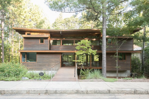 Front yards with older and newer trees create privacy, and granite curbs along the sidewalk indicate the community's attention to quality and detail.  Photo 8 of 11 in An Eco-Friendly Community Outside of Atlanta Celebrates Nature and Sustainability