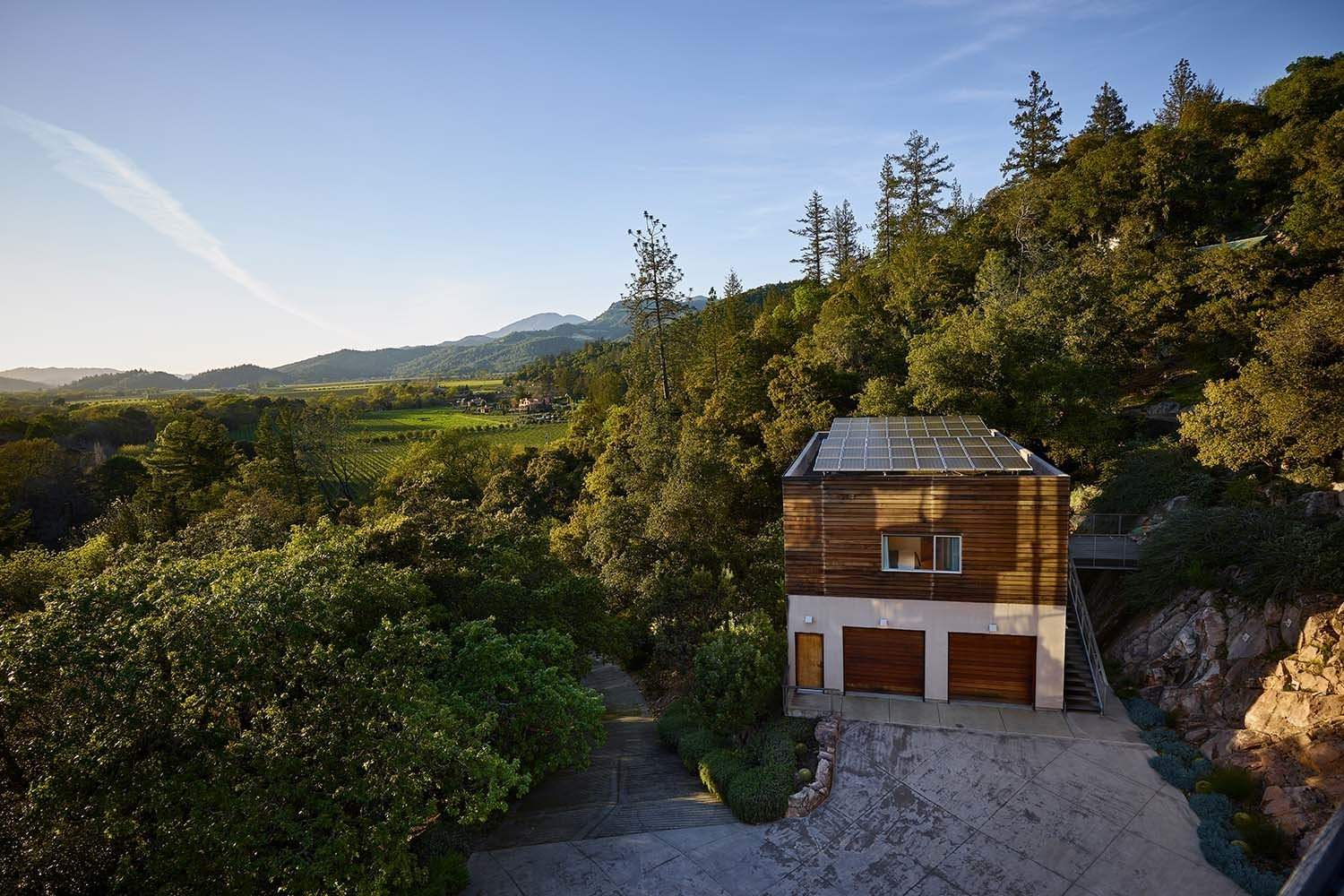 Outdoor, Slope, Trees, Grass, Shrubs, Walkways, Boulders, Stone Patio, Porch, Deck, and Hardscapes  Photo 3 of 14 in Discover a Nature-Immersed Retreat For Sale in the Heart of Wine Country