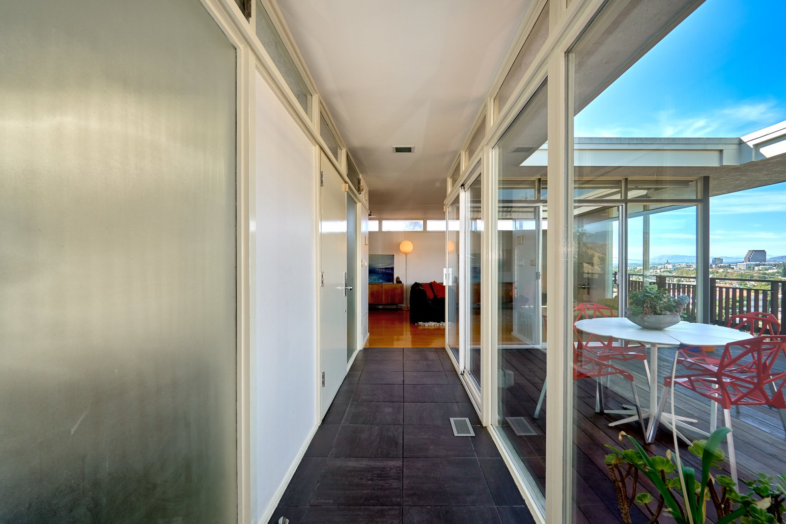 A narrow hallway with black slate tiles connects the two wings of the house.  Photo 10 of 14 in A Midcentury-Modern Home in L.A. Designed by Richard Banta Is For Sale For $899K