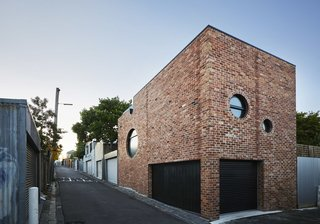 On a rear addition to an existing suburban home outside of Melbourne, Australia, Austin Maynard Architects designed a brick structure with a series of round windows on multiple facades. The circular windows vary in size and location, giving the building a playful twist, despite its more traditional construction of red brick.