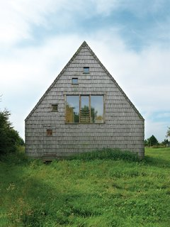 "At this wooden A-frame retreat in the Normandy region of France, architect Jean-Baptist Barache designed a home that's both casual and elegant, low-key and surprising. A large central window on one of the end gables of the house is accompanied by a scattering of smaller, square ""peek-a-boo"" windows. The two windows on the third floor bring light and views into the bedroom, and the window on the first floor fits perfectly into the camouflaged rear door."