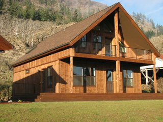 "At 939 square feet on the main floor, the ""Get-Away"" cabin by TLC Modular Homes also features about 150 square feet of an outdoor covered deck and a lofted second floor. TLC Modular Homes, while based in Goldendale, Washington, services areas in both Oregon and Washington state, and they offer modular homes that vary from more traditional styles like Cape Cod homes to smaller, rustic cabins, all made in their proprietary factory that opened in 2000."