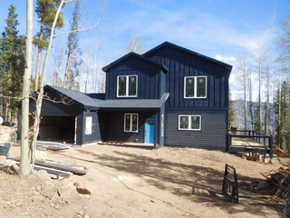This mountain cabin by Liscott Custom Homes was designed as a three-bedroom, three-bath custom home for a family in Silverthorne, Colorado. Measuring 2,400 square feet, the home is clad in contrasting horizontal and board and batten siding coated in a dark, blue-gray finish.
