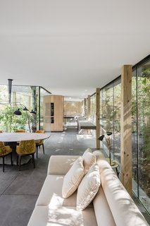 A Portuguese Glass House Uses Surrounding Foliage as a Privacy Screen - Photo 8 of 15 - A neutral palette for furniture keeps the interior feeling light and sun-drenched.