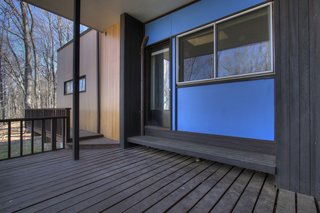 "The exterior is clad in ""Breuer blue"" panels, tongue-and-groove vertical cypress siding, and generous expanses of windows with curated views to the landscape beyond."