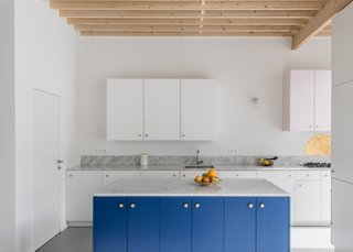 The kitchen's white palette allows the bright blue cabinets and gold hardware to stand out.