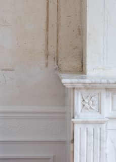A detail of the historic marble fireplace and original plaster in the more formal rooms that look out onto the street.
