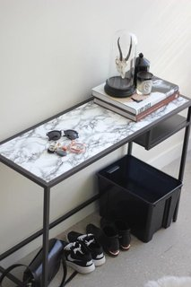 Some black spray paint and marble contact paper easily transform this table.