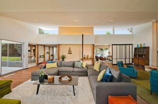 The entry opens out onto the oversized living room, with its high ceilings, floor-to-ceiling glazing, and ample space for multiple seating arrangements.