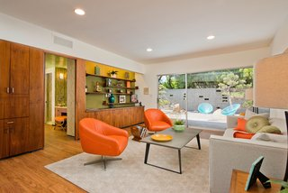 The den has a wall of custom wood cabinetry with original midcentury hardware.
