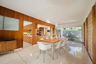 The dining room opens to the kitchen, which features glazing to the yard. The flooring here is the original terrazzo.