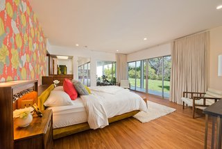 The master bedroom has windows and glass doors that open onto the back yard. The wood floors in this room are new.