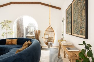 The handmade tile and artwork pick up the blue from the sofa and continue it throughout the space.