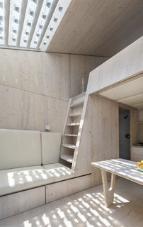 The interior is clad in wood, with a lofted bed at the taller end of the unit.