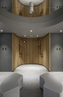 Terrazzo floors and benches are paired with an open wooden shower in the hotel's sauna.
